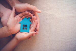Hands,Holding,Paper,House,,Family,Home,,Homeless,Shelter,And,Real
