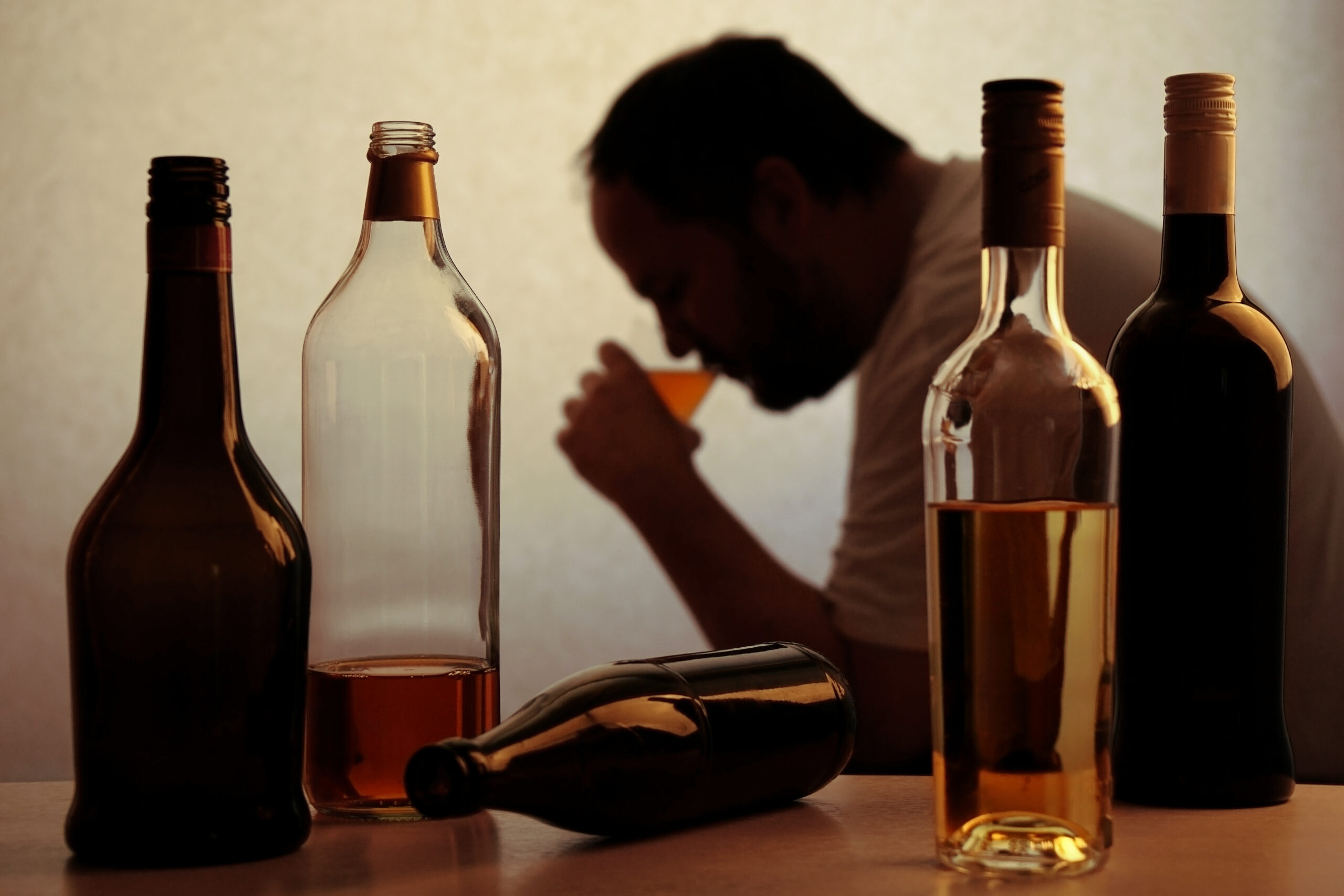 Silhouette,Of,Anonymous,Alcoholic,Person,Drinking,Behind,Bottles,Of,Alcohol