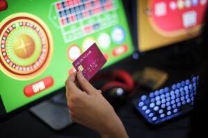 Hand,Holding,Credit,Card,Playing,Online,Gambling